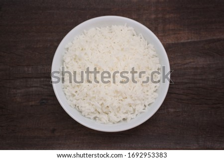 Jasmine cooked rice in white bowl on wooden background using as healthy food, thai food concept. top view #1692953383