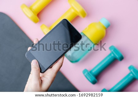 Hand taking a picture of four colored dumbbells and reusable plastic bottle of water lying on a mat in a row. Using a cell phone. Top view.
