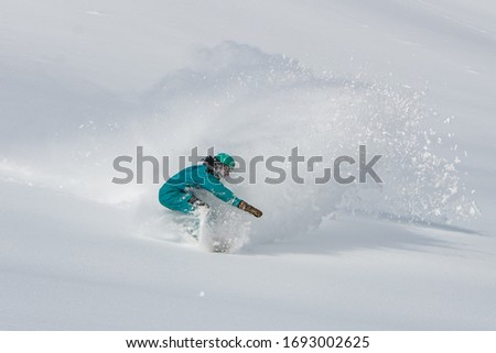 A snowboarder making a powder turn in deep snow on a forest meadow on a sunny morning #1693002625