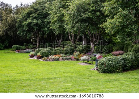 A garden landscape design featuring lawns, trees, evergreen topiary bushes and flower bed #1693010788