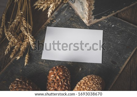 Close up of mockup blank on background of homemade bread making. Mockup of brochure or greeting card in harvest composition with empty place for text.