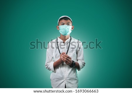 Coronavirus Covid-19 and Air pollution pm2.5 concept. Muslim young men who are praying and wearing hygiene protective mask for protect pm2.5. epidemic virus symptoms with green background #1693066663