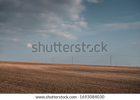 Spring field landscape. Blue sky with white clouds in background. Freshly plowed fields and electric poles. #1693084030