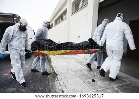 Funeral Home employees wear protective suits to protect themselves from Coronavirus, as they carry a dead body inside Bag. Royalty-Free Stock Photo #1693125517