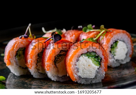 sushi roll with salmon, avocado, cream cheese in plate on black wooden table background #1693205677