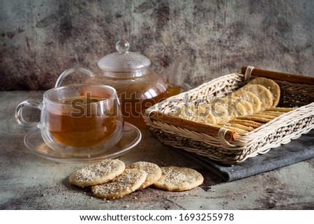 Sesame crackers in a wicker basket on a gray background, a Cup of hot tea and a teapot with tea on a gray background #1693255978