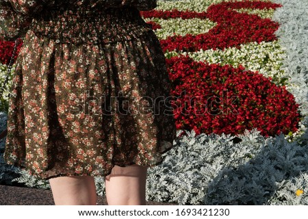A young lady is standing against a city flowerbed with flowers. #1693421230