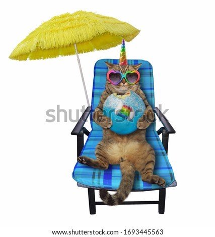 The beige cat unicorn in heart shaped sunglasses is sitting in a blue beach chair and eating a donut under a yellow umbrella.. White background. Isolated.