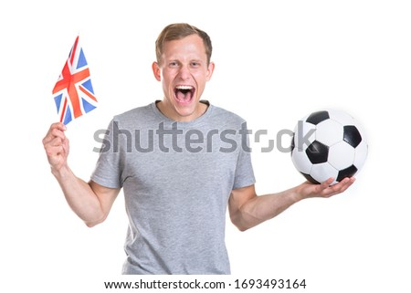 Happy young male football fan shouts out. Man with a soccer ball and the flag of the United Kingdom is isolated on a white background and is looking at the camera.