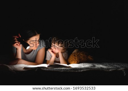 happy family mother and child son reading a book with a flashlight. Family before going to bed mother reads to her child son book near a flashlight in the evening. Royalty-Free Stock Photo #1693532533