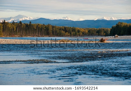 Wild far est river, Autumn landscape with snow picks mountains. Travel camp on the wild river #1693542214