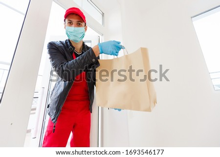 delivery man in protective mask and medical gloves holding a paper box. Delivery service under quarantine, disease outbreak, coronavirus covid-19 pandemic conditions. #1693546177