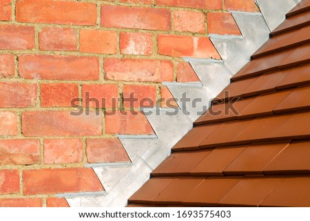 Closeup of new plain red clay tiles and lead flashing on a pitched roof in the UK Royalty-Free Stock Photo #1693575403