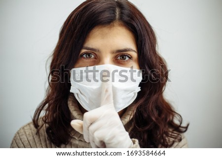 Portrait of young woman holds on her finger showing silence sign and has to stay home during quarantine due to coronavirus pandemia. Beautiful girl wearing medical mask and gloves. Covid-19 epidemia #1693584664