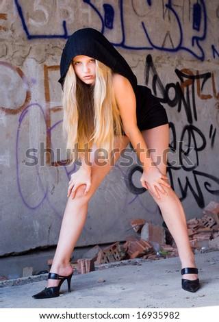 Beautiful grungy girl posing at graffiti wall #16935982