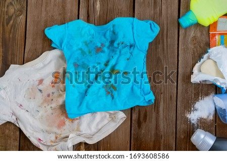 Dirty children's clothes are scattered on a wooden table next to washing powders and soap.Concept washing dirty spots, the best means of cleaning kids clothes. Royalty-Free Stock Photo #1693608586