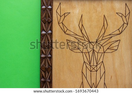 A part of wooden picture with the image of a deer made using the technique of pyrography and decorated with a carved frame. On green background with place for text