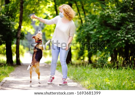 Young beautiful woman wearing disposable medical face mask playing with Beagle dog in the park during coronavirus outbreak. Walking of pets. Safety in a public place while epidemic of covid-19. Royalty-Free Stock Photo #1693681399