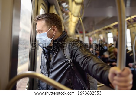 Mature man wearing disposable medical face mask in car of the subway in New York during coronavirus outbreak. Safety in a public place while epidemic of covid-19. #1693682953