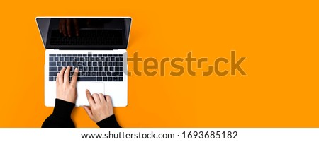 Person using a laptop computer on a solid color background Royalty-Free Stock Photo #1693685182