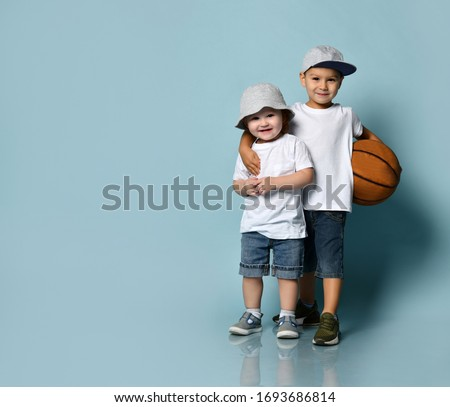 Little brunet boy hugging his toddler brother or sister. They dressed in casual clothes. Elder one holding basketball ball, smiling posing on blue background. Childhood, sport. Full length, copy space