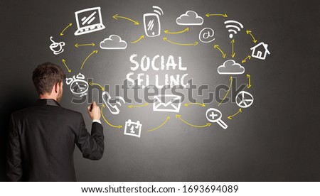 businessman drawing social media icons with SOCIAL SELLING inscription, new media concept #1693694089