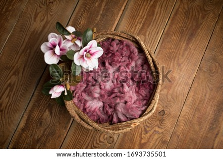 Newborn photography digital background prop. wicker basket with pink fur and flowers on a wooden background.