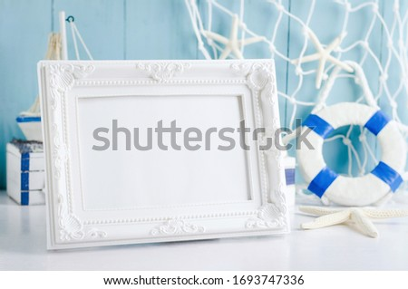 Close up of vintage picture frame with sail boat Toy model, rope and seashell on white and blue wooden background - Nautical background