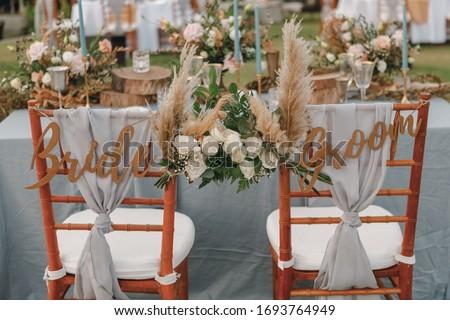 Two chairs assigned to the bride and groom at a wedding setting. Bride and groom. Wedding bride and groom Signs on chairs standing in the woods. #1693764949
