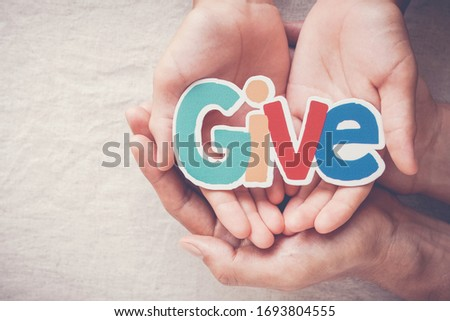 Adult and child hands holding Give word, kind, donate, charity and compassion concept #1693804555