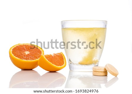 Series of orange flavored vitamin c effervescent tablet dropped and dissolve in glass of water on white background