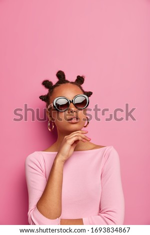 Beautiful dark skinned young woman keeps hand under chin, wears trendy summer sunglasses and stylish jumper, makes fashion photography, models in studio against pink background. Vogue, style Royalty-Free Stock Photo #1693834867