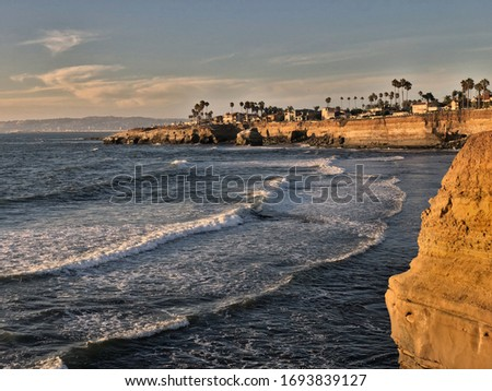 Golden hour shot at Sunset Cliffs, San Diego, California. Small rock cliffs with palms on it with ocean waves in the foreground.