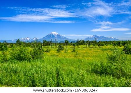 Panoramic view of the city Petropavlovsk-Kamchatsky and volcanoes: Koryaksky Volcano, Avacha Volcano, Kozelsky Volcano. Russian Far East, Kamchatka Peninsula. #1693863247