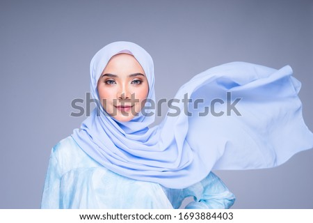Muslim woman wearing traditional wear and hijab isolated on grey background. Hijab is creatively made flying. Idul Fitri and hijab fashion concept. Royalty-Free Stock Photo #1693884403