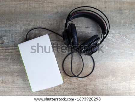 Headphones and book. The book has a cover in the form of a mockup flag. Concept audiobooks. Learning languages. #1693920298