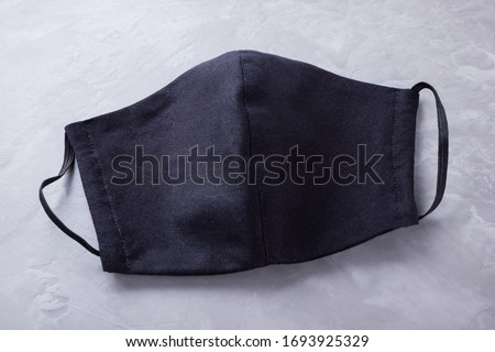 Handmade protective mask. Antivirus mask made from black cotton. Black face mask during a pandemic virus COVID-19. Face protective mask on a gray background #1693925329