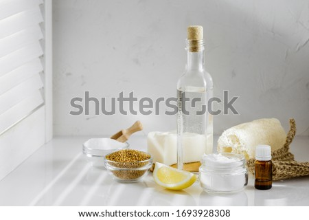 Eco friendly tools and ingredients for DIY house cleaning. White vinegar, baking soda, mustard seeds, lemon, solid natural soap, aroma oil and luffa sponge on the kitchen white table Royalty-Free Stock Photo #1693928308