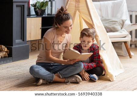 Smiling mother tell fairytale to son at home. Good family pastime on weekend. Adopted child and baby sitter. Mom read interesting story schoolboy kid. Wigwam in cozy living room. Educational process #1693940338