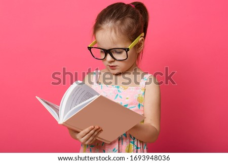 Picture of thoughftul hard working smart little girl wearing eyeglasses and dress, holding book, turning over pages, looking for information, studying alone, being curious. Knowledge concept.