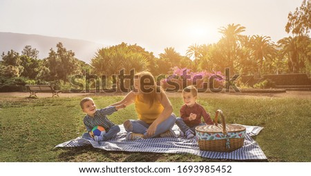 Young mother with her twin brother sons - Family having a picnic in a park outdoor - Love and fun time between mom and her children