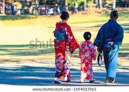 Japanese family walking in the Park. Parents walk with their daughter on a Sunny day. Japanese national costumes. The picturesque clothing of the people of Japan. Kimono for men and women. Royalty-Free Stock Photo #1694023963