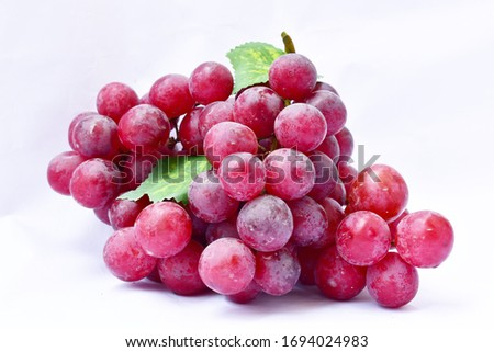 Red grape, large fresh grape fruit with green leaves on a white background #1694024983