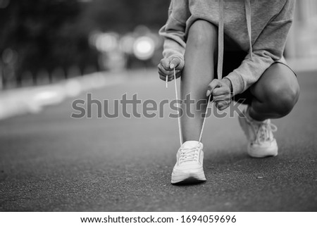 young athlete. beautiful girl athlete tying shoelaces on sneakers. beautiful girl athlete sitting tying shoelaces on white sneakers. Healthy lifestyle concept. black and white photo