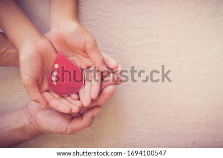 Hands holding blood drop,  give blood donation, blood transfusion, world blood donor day, world hemophilia day concept #1694100547