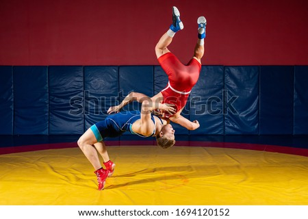 Two  strong men in blue and red wrestling tights are wrestlng and making a suplex wrestling on a yellow wrestling carpet in the gym. Wrestlers doing grapple.  #1694120152