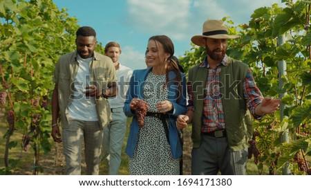 Group of beauty fashion friends walking with farmer on wine tour through gorgeous grapevine garden talking enjoying summertime at vineyard. Royalty-Free Stock Photo #1694171380