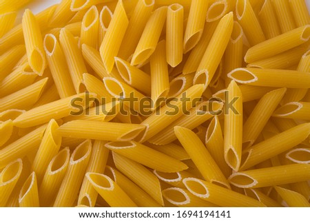 Penne pasta background. Pasta Penne texture background. Tube like macaroni. Heap of pasta. Top view. Delicious pasta. #1694194141