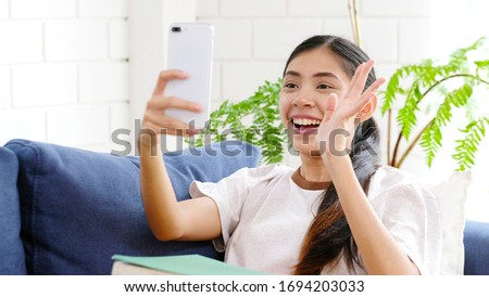 Video call conference, Happy girl having a video chat on mobile phone at home, Asian woman talking video call on a smartphone, Female people greeting with family, friend by online, Social distancing #1694203033