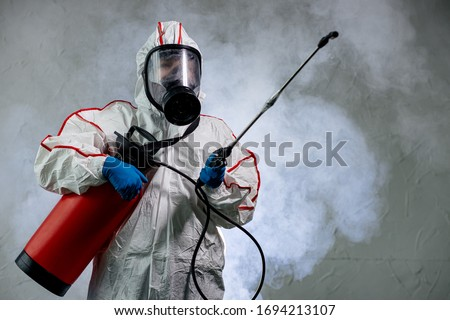 professional disinfector in an NBC personal protective equipment ppe suit, gloves, mask, cleaning isolated space with pressurized spray disinfectant water to remove covid-19 coronavirus #1694213107